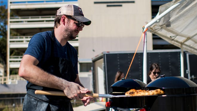 Chef Jeremy Conner removes a pizza from an oven at Olympic Grove in Lafayette, La., Saturday, Dec. 5, 2015. The pop-up beer garden is located at the corner of West St. Mary and St. Landry Streets in Lafayette.