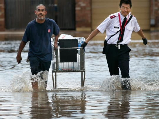 Jose Patino (left) and Richard Wang of the Salvation Army transport water and ice to residents on the flooded street of S. Doran, just east of Stapley Drive.