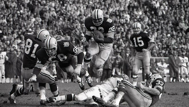 Green Bay Packers running back Elijah Pitts (22) follows guard Gale Gillingham through the hole against the Atlanta Falcons at Lambeau Field on Oct. 26, 1969.