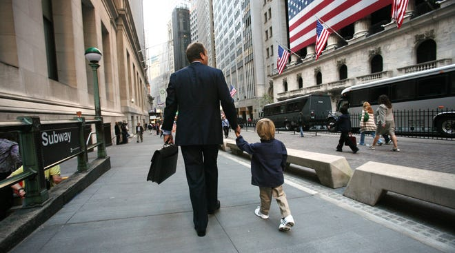 A businessman walks with his son past the New York Stock Exchange in New York.