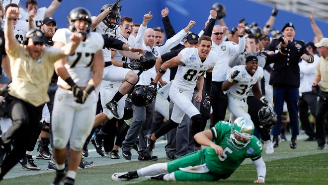 North Texas quarterback Alec Morris (5) looks on as Army celebrates their 38-31 win in overtime in the Heart of Dallas Bowl NCAA college football game Tuesday, Dec. 27, 2016 in Dallas.