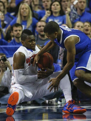 UK's Aaron Harrison battles Florida's Will Yeguete for a loose ball in the first half of Sunday's SEC tournament championship game at the Georgia Dome.