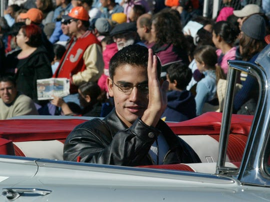 Parade grand marshal Alejandro Hernandez waves from a 1960s-era convertible Nov. 25, 2004. UTEP basketball coach Don Haskins, Jessica Silva and Rene Hernandez Armijo were honorary grand marshals.