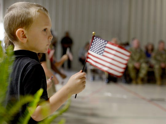 Malesus Elementary pre-K student Hunter Coenen waves his American Flag as fellow students sang during the school's 14th Anual Veterans Day Program, Friday.