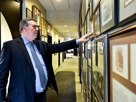 Carl Hughes points to a historical collection inside Fahey Bank. The CEO and Board Chairman of the company was removed from office on Thursday in a reshaping of the company's executive team.