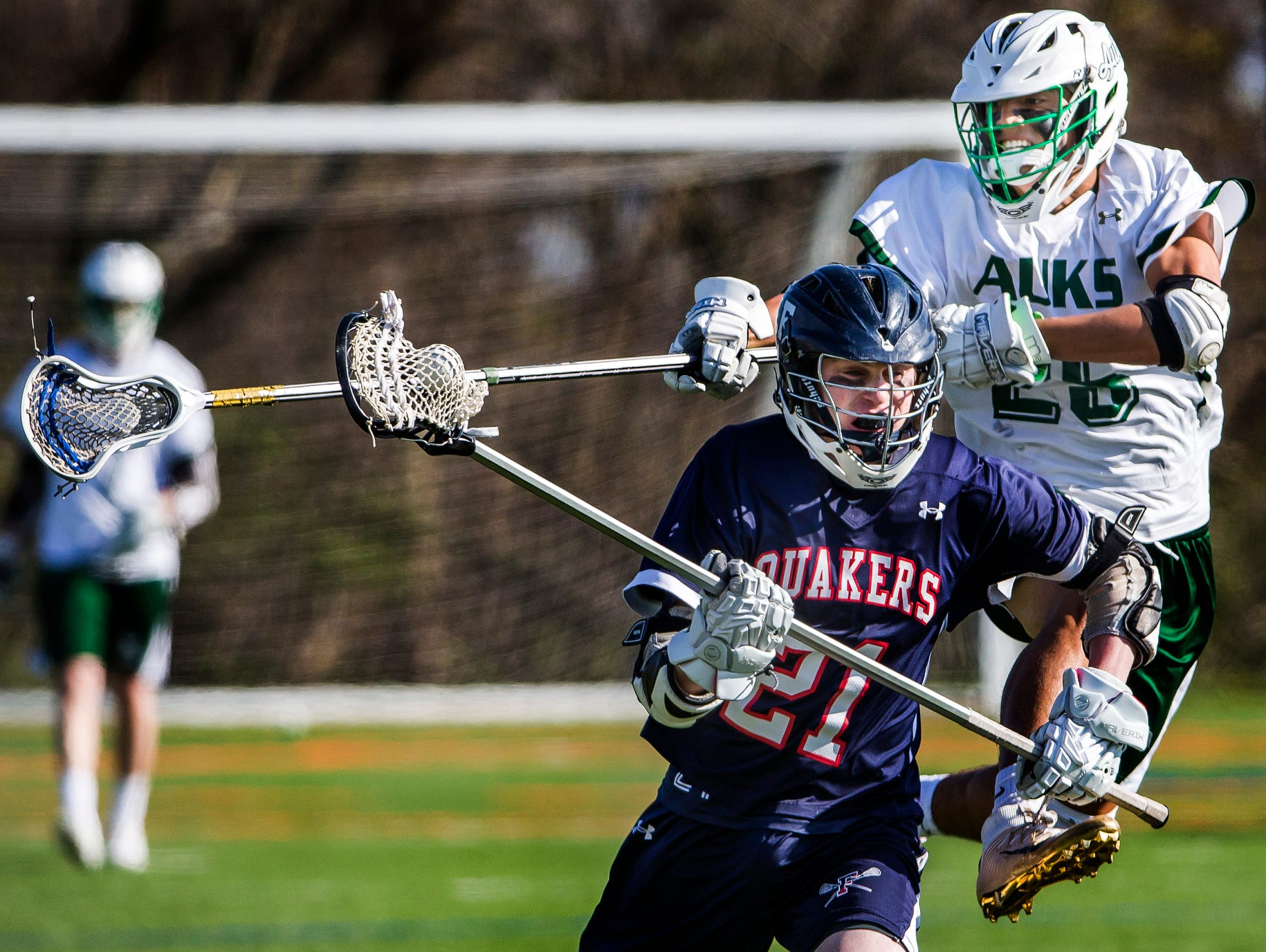 Archmere's Nicholas Salameda leaps behind Friends' Thomas Manley as he tries to knock the ball away in Archmere Academy's 13-8 win over Wilmington Friends School at Archmere on Thursday afternoon.