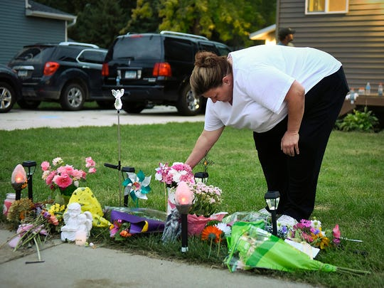 Brenda Carlson of Watkins placed a bouquet of flowers on a memorial in front of the Ertl home on Tuesday before a candlelight vigil for Alayna Ertl.