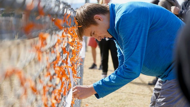 Freshman Andrew Pavicich, 15, ties an orange ribbon onto a fence at Columbine High School in Littleton, Colo. following a gun-violence walkout on March 14, 2018.