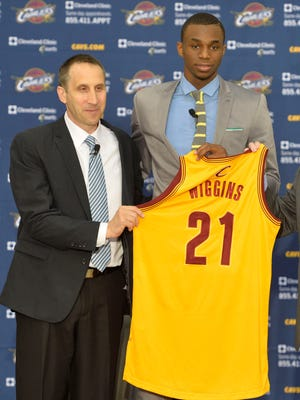 Andrew Wiggins holds up his Cavaliers jersey at a news conference after being drafted.