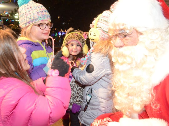 Wayne children telling Santa what they want for Christmas at the tree-lighting ceremony on Dec. 8, 2016. Pictured is Elise pointing to Santa and telling him they will have cookies waiting for him on Christmas eve. Also pictured are Camille, Shayna and Brianna.