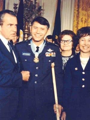 Leo Thorsness receives Medal of Honor from President Nixon in October 1973. Gaylee, his wife, smiles to his right.