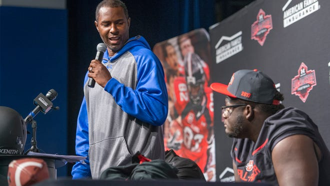 Coach Charlie Ward speaks during the event announcing that football player Alex Leatherwood, right, has been selected for the annual Under Armour High School All-America Game at Booker T. Washington High School in Pensacola on Wednesday, October 12, 2016.  The game featuring more than 90 of the nation's best senior high school football players will be played on January 1, 2017.