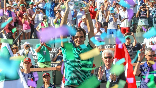 Roger Federer holds the trophy in a hail of confetti after winning BNP Paribas Open, March 18, 2017.