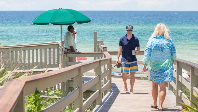 Jacob Marek, of Austin, Texas, center and fellow beachgoers make their way through a private gated and security guarded walkover at Rosemary Beach in Walton County, Florida on Wednesday, July 19, 2017.