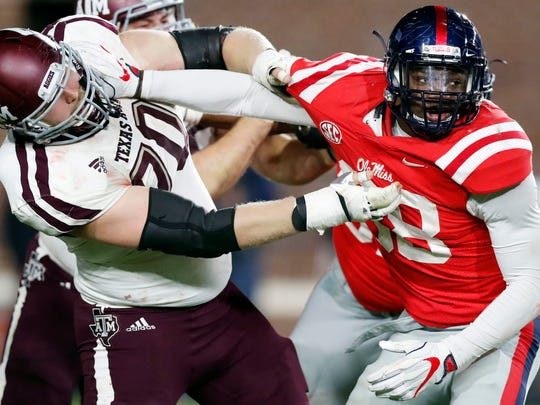 Texas A&M offensive lineman Connor Lanfear (70) holds up Mississippi defensive end Marquis Haynes (38) during the second half of an NCAA college football game in Oxford, Miss., Saturday, Nov. 18, 2017. Texas A&M won 31-24. (AP Photo/Rogelio V. Solis)