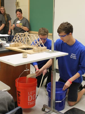 Hunter Davis, left, steadies a bucket suspended from a wooden bridge while teammate Tyler Hartman pours sand into the bucket to test the strength of the bridge. The Pearl River Central High School sophomores competed Saturday, Feb. 21, in the 2015 Mississippi Gulf South Regional Science Olympiad held at Pearl River Community College. Their bridge did not break when it was holding all the available sand for a weight of 15.3 kilograms. The Pearl River Central team placed third in the high school division and advances to state competition.PRCC Public Relations photo
