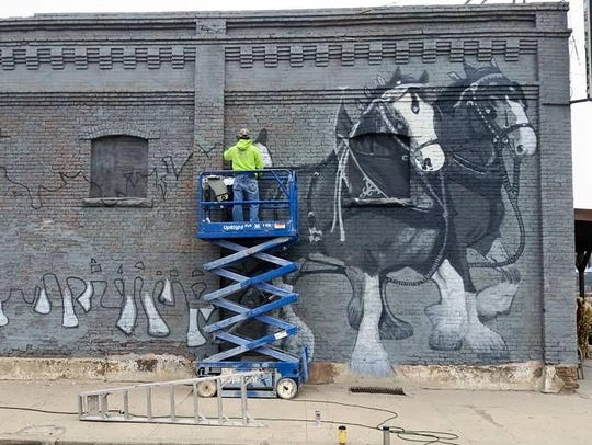 Andrew Fowler paints on the side of Ed's Tavern in