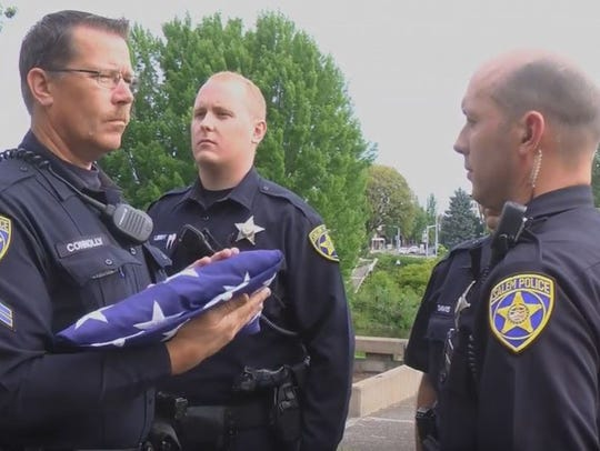 Members of Salem Police Department fold American flags