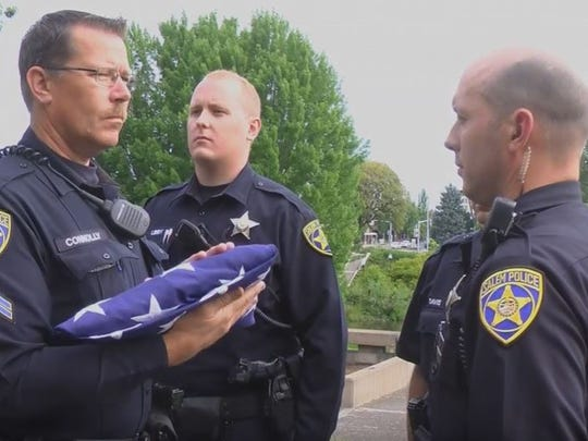 Members of Salem Police Department fold American flags on Friday, June 3, 2016.