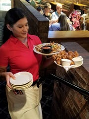 Server Susan Doss delivers fried mushrooms and cheese fries to a table in Rafferty's on Green River Rd.