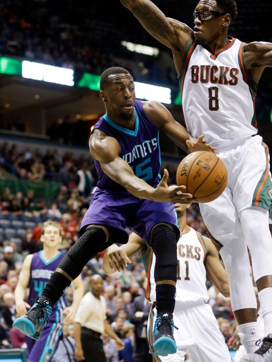 Charlotte Hornets' Kemba Walker tries to pass around Milwaukee Bucks' Larry Sanders (8) during the first half of an NBA basketball game Tuesday, Dec. 23, 2014, in Milwaukee. (AP Photo/Morry Gash)