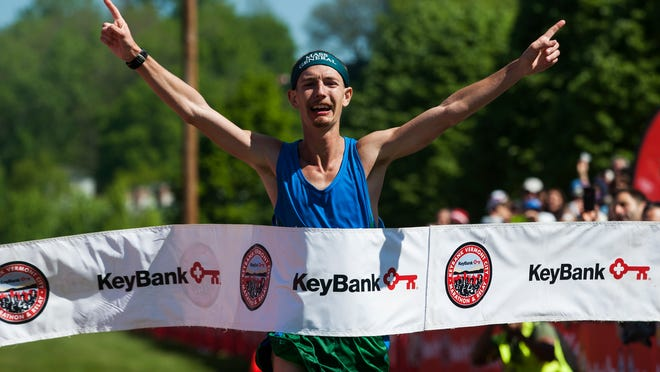Tyler Andrews of Concord, Mass., crosses the finish line in first place in the elite men's division at the 26th Keybank Vermont City Marathon.