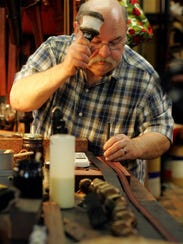 Dennis Knight customizes a leather belt for a customer