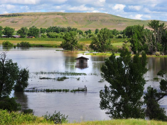 A pump house is surrounded by rising floodwater on the Sun River south of Vaughn Wednesday morning.