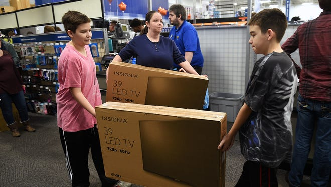 Susie Spriggs, with the help of her sons Jonathan and Alex, purchases two TVs from Best Buy in West Nashville on Thanksgiving night Nov. 26, 2015.