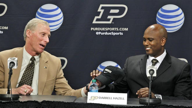 Athletic Director Morgan Burke hands Darrell Hazell a cap as Hazell is named new head football coach during a press conference Wednesday, December 5, 2012, at Mackey Arena.