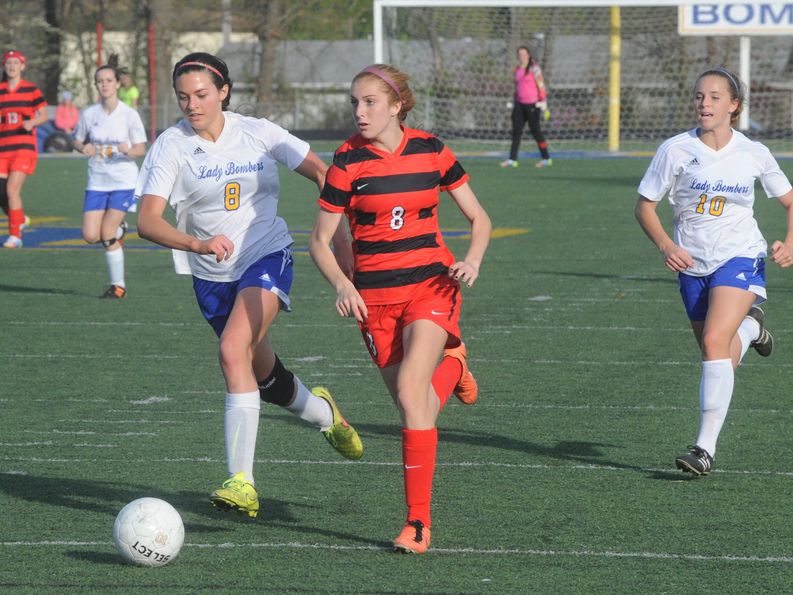 Mountain Home's Jessica Swonger, left, races Cabot's Tristyn Edgar to the ball during the Lady Bombers' 1-1 tie with the Lady Panthers on Friday at Bomber Stadium.