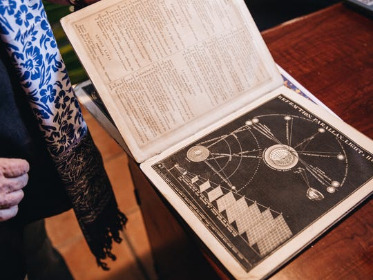 Ahead of an astrology reading, Dana Haynes flips through an old astrology book in her home office.