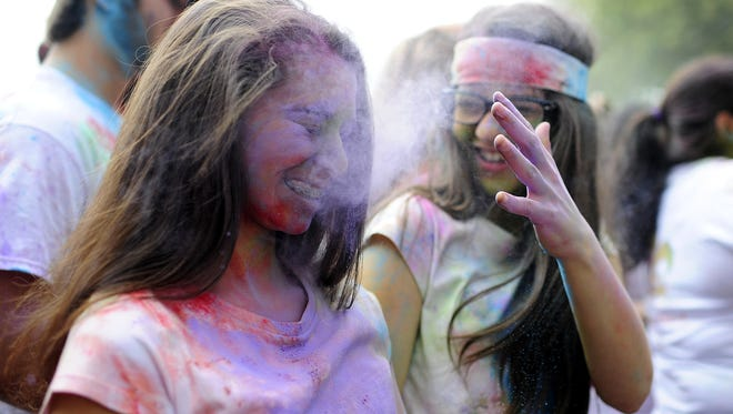 Rachel Viola, 13, tosses purple powder onto Mya McGinnis, 13, during the Holi Festival at Girard Park in Lafayette on Saturday. Holi is a traditional Hindu celebration of spring. Paul Kieu, The Advertiser Rachel Viola, 13, tosses purple-colored powder onto the face of Mya McGinnis, 13,  during the Acadiana Indian Association's Holi Festival at Girard Park in Lafayette, LA, Saturday, March 29, 2014. Holi, also known as the Festival of Colors, is a traditional Hindu celebration to celebrate the arrival of spring.  Paul Kieu, The Advertiser