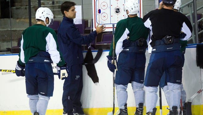 Ice Flyers head coach, Kevin Hasselberg, center, holds a meeting a center ice with his players during practice Wednesday afternoon. The Ice Flyer will begin their 2016 season with a home opener against Fayetteville.