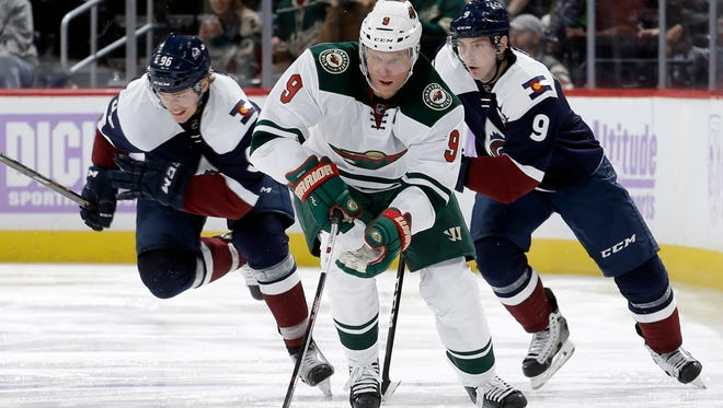 Minnesota Wild center Mikko Koivu moves the puck up the ice against the Colorado Avalanche's Mikko Rantanen (96) and Matt Duchene (9) during the second period of an NHL hockey game, Saturday, Nov. 5, 2016, in Denver. (AP Photo/Jack Dempsey)