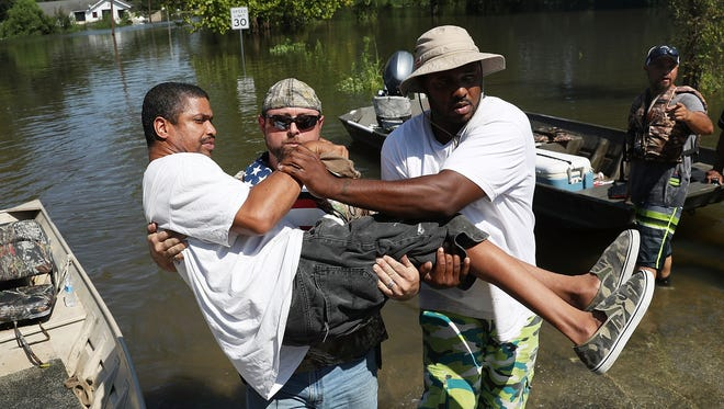 Quintin Sanders is carried to dry land by volunteer rescuers after his neighborhood was inundated with the flooding of Hurricane Harvey on Aug. 31, 2017, in Beaumont, Texas.