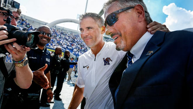 University of Memphis head coach Mike Norvell (middle) and Athletic Director Tom Bowen (right) celebrate as they walk off the field after defeating national ranked UCLA 45-48 at The Liberty Bowl Memorial Stadium in Memphis, Tennessee., Friday, September 16, 2017.