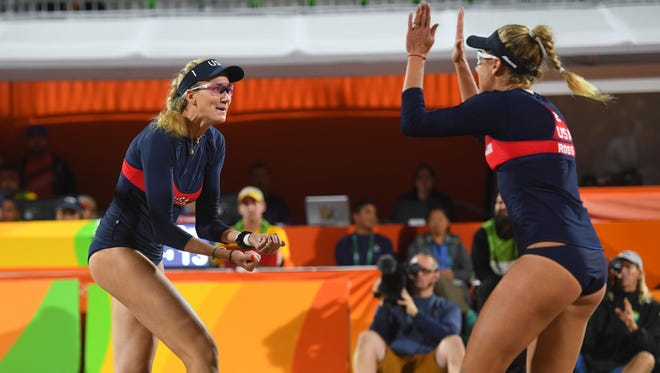 Kerri Walsh Jennings and April Ross celebrate in a women's beach volleyball Round of 16 match.