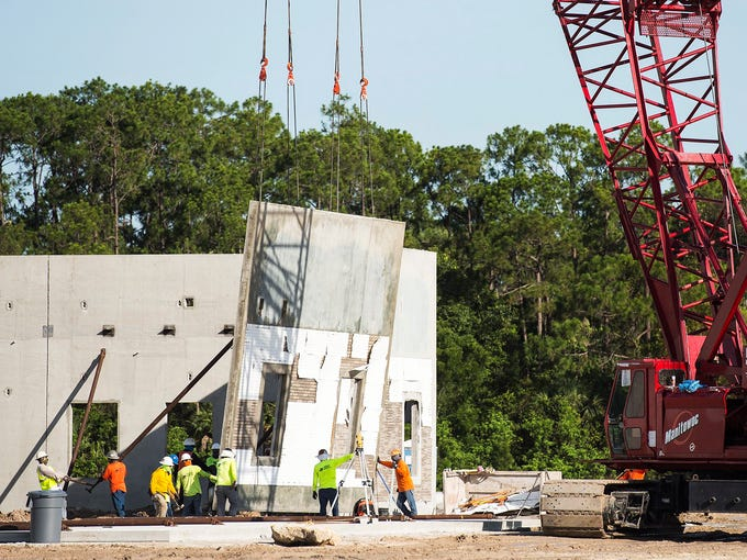 Workers watch as a crew prepares to put up a panel