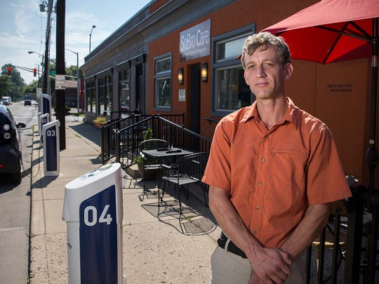 Owner Helger Oomkes poses in front of SoBro Cafe, where BlueIndy has installed a station of five parking spots for the rentable smart cars, occupying a stretch of public parking along 52nd Street in front of his restaurant's entrance, Indianapolis, Monday, July 31, 2017.