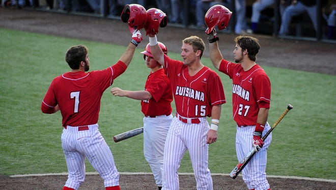 """UL third baseman Ryan Leonards (7) celebrates at home plate with outfielders Dylan Butler (15) and Seth Harrison (27) after Leonards hit a home run during the fourth inning of the Cajuns? 10-1 win over Northwestern State at Tigue Moore Field.  Paul Kieu/The Advertiser UL utility player Ryan Leonards (7) celebrates at home plate with outfielders Dylan Butler (15) and Seth Harrison (27) after Leonards hit a home run during the fourth inning of an NCAA baseball game at M.L. """"Tigue"""" Moore Field in Lafayette, LA, Tuesday, March 25, 2014. Butler (15) also scored off of the home run."""