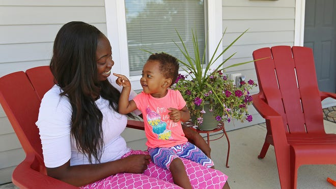 Ronnisha Davis and her daughter Mackenzie, 1, on the front porch of her home, Monday, July 11, 2016.