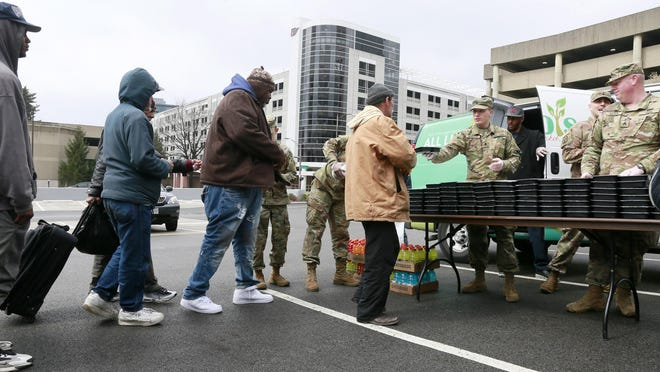 The Ohio National Guard formed an assembly line to serve meals to the homeless outside the YMCA in Downtown Columbus on March 24.