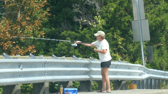 A woman fishes from the Nanaquaket Bridge in Tiverton on Saturday. Because of complaints and potential danger, town officials are asking the state Traffic Commission to prohibit the practice.