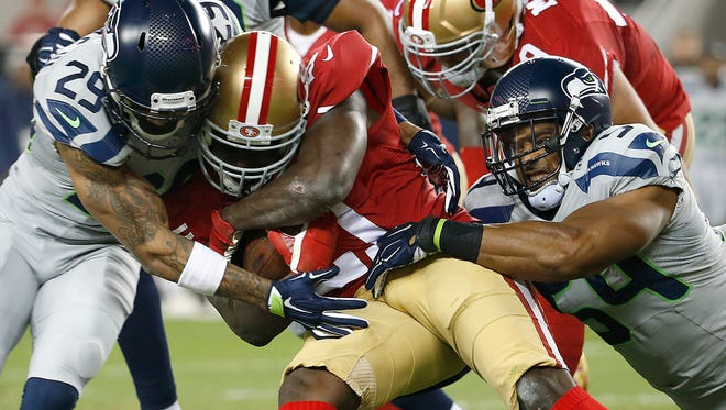 San Francisco 49ers running back Frank Gore, center, is tackled by Seattle Seahawks free safety Earl Thomas (29) and middle linebacker Bobby Wagner (54) during the first quarter of an NFL football game in Santa Clara, Calif., Thursday, Nov. 27, 2014.