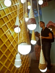 A waffle light wall featuring a series of hanging ice cream cones light bulbs at the Museum of Ice Cream, in New York.