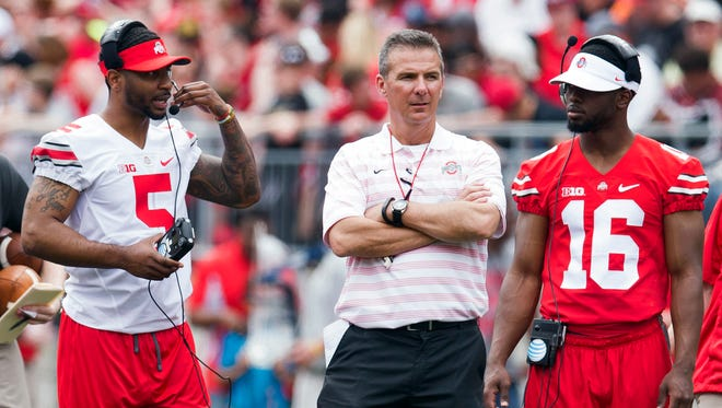 Ohio State quarterbacks Braxton Miller (left) and J.T. Barrett (right) with coach Urban Meyer at the Buckeyes' spring game.