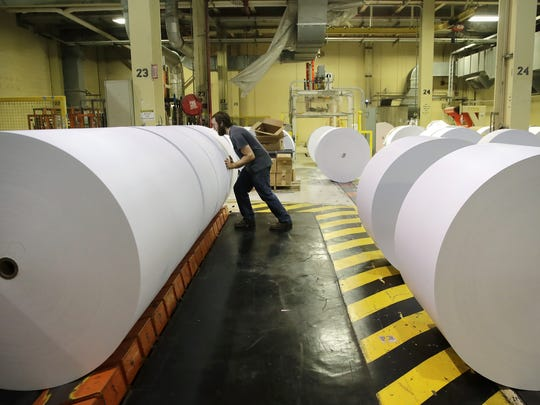 David Lee, a fourth hand at Midwest Paper Group, formerly Appleton Coated, works Wednesday with the No. 7 paper machine winder to get paper rolls ready for roll wrapping and shipping.