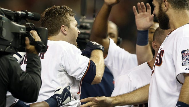 Minnesota Twins second baseman and former Southern Miss star Brian Dozier, left, is swarmed by teammates Monday after his two-run, walk off home run in the 10th inning of the Twins' game against the Baltimore Orioles.