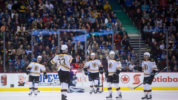 Boston Bruins defenseman Zdeno Chara (33), of Slovakia, celebrates his goal with teammates Dominic Moore, from left, Jimmy Hayes, Peter Cehlarik, of Slovakia, and Kevan Miller during the second period of an NHL hockey game in Vancouver, British Columbia, Monday, March 13, 2017. (Darryl Dyck/The Canadian Press via AP)